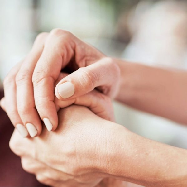Cropped shot of a nurse holding an elderly woman?s hands in a retirement home
